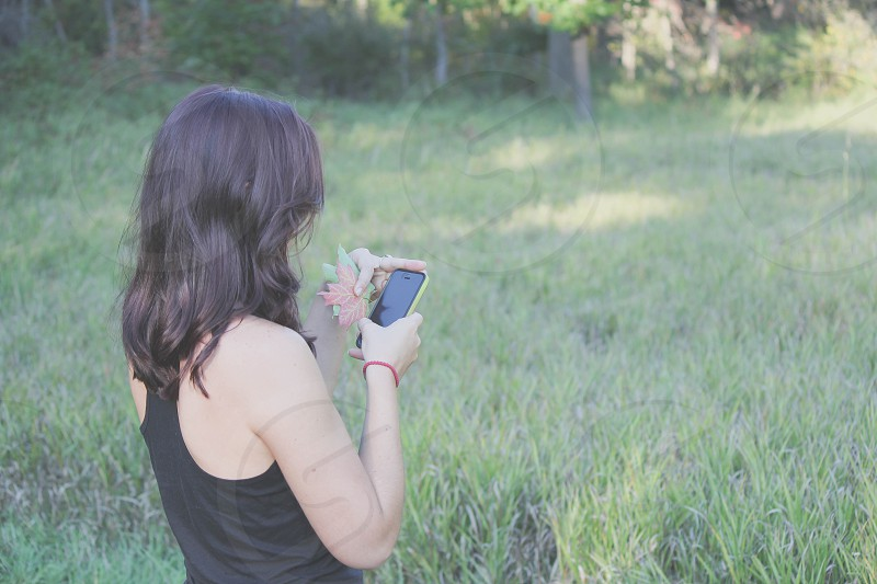 woman wearing black racer back top with cell phone photo
