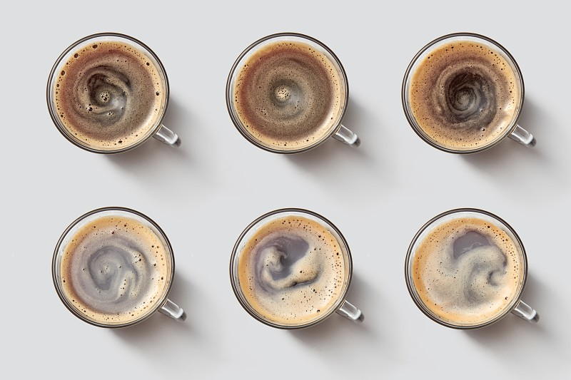 Top view on many glass cups with coffee and foam on a gray background. Fragrant morning coffee photo