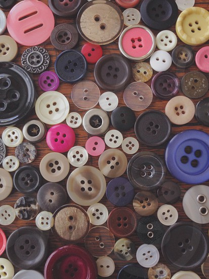 An grouping of buttons scattered on a table photo