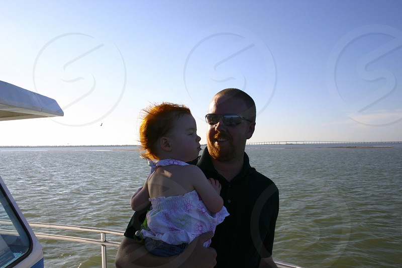 Father and daughter enjoying the ocean breeze from the deck of a boat. photo