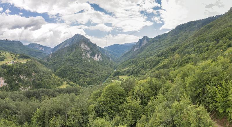 Mountain range and small village houses in green forest near Tara river canyon view from Djurdjevica Tara Bridge Montenegro photo