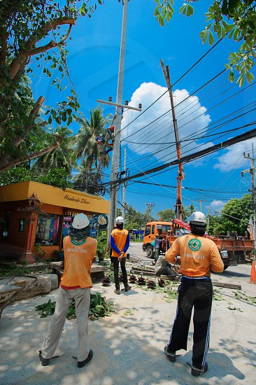 Thai style construction worker. Electric guy at work photo
