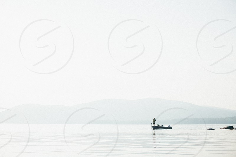 canoe in ocean water near mountains on foggy weather photo