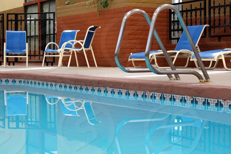 blue pool chairs near swimming pool photo