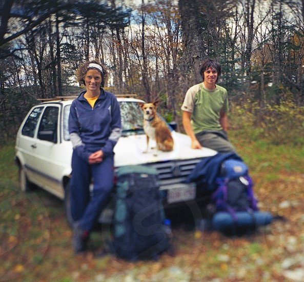 young couple camping with their dog. tilt / shift image photo