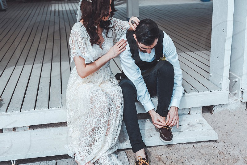 man in black vest black pants and teal dress shirt tie his shoes beside woman wearing white lace flora dress fixing his vest photo