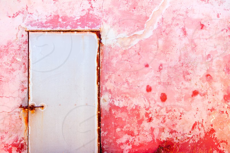 Pink mediterranean grunge door and wall with weathered texture photo