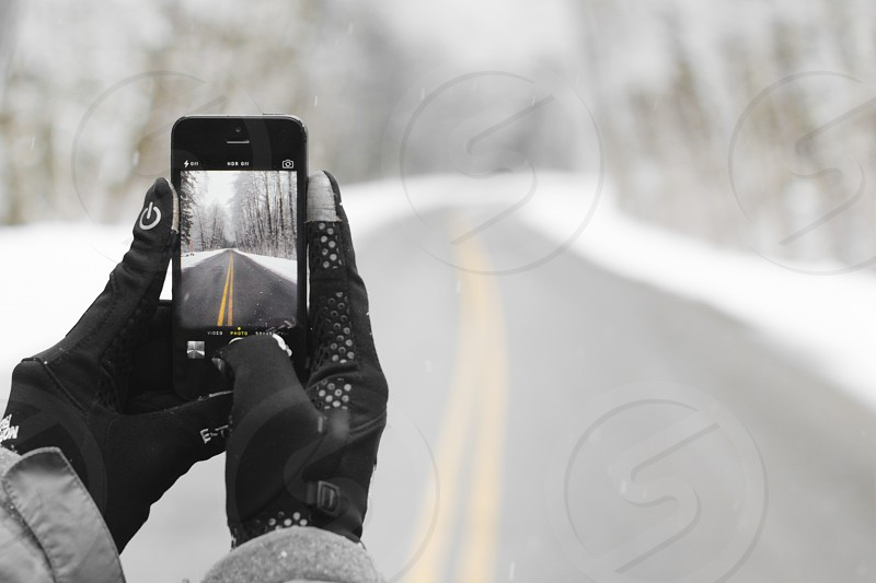 person holding iphone 5 capturing road photo