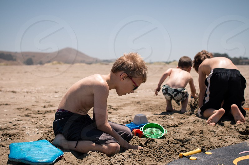 3 topless boys playing with sand in tilt shift lens photo