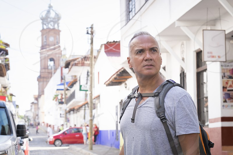 Tourist in Puerto Vallarta Mexico. Man with backpack 55 years old hispanic ethnicity. photo