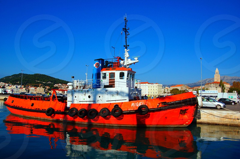 orange and white ship on body of water during daytime photo