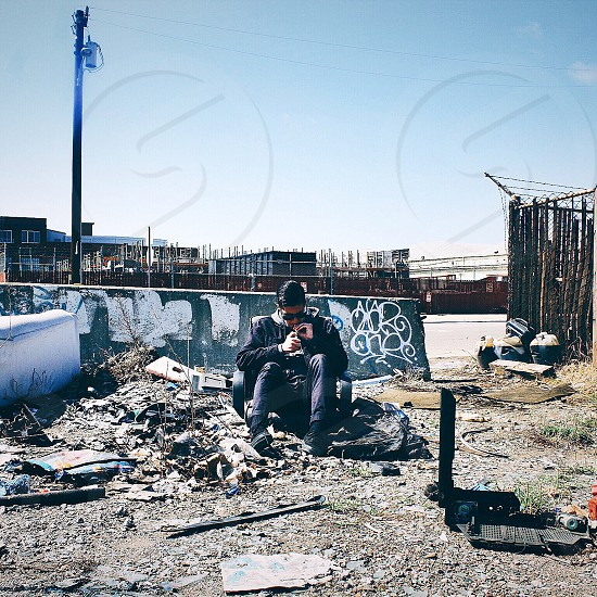 man in black leather jacket and black pants sitting on dirt pil near a concrete post during daytime photo