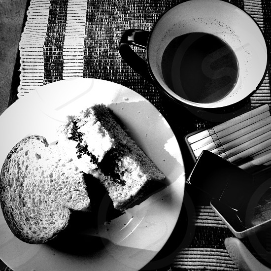grayscale photography of mug beside plate of pastry and cigarette sticks photo