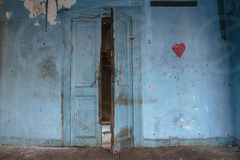 Blue door in old abandoned building with heart drawing on wall photo