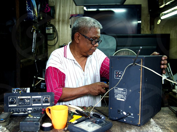 ANTIPOLO CITY PHILIPPINES - NOVEMBER 30 2018: A technician repairs an electronic household item in his repair shop. photo