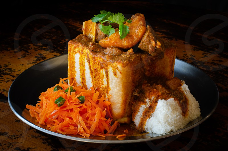A Durban Bunny Chow - or in this case a quarter mutton bunny - served with sambals. This is an iconic Durban meal consisting of a section of a loaf of bread hollowed out and filled with mutton curry and gravy. The sambals are grated carrot with chopped chilli. The meal is traditionally eaten with one's fingers. Picture: Jonathan Oberholster photo