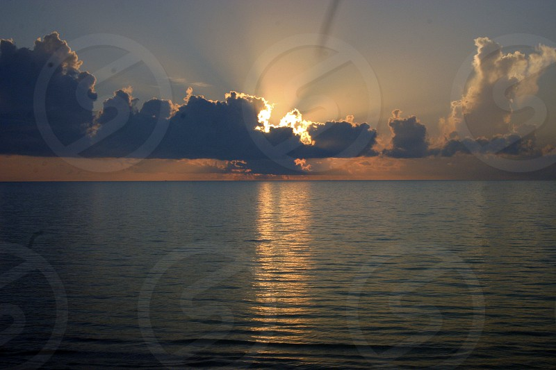 Sun setting on the ocean with dramatic clouds reflection on the sea and light flares from the clouds. photo