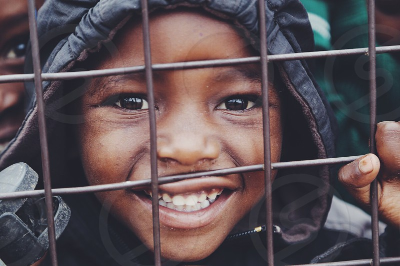 Street kid from Kenya smiles with hope in his eyes while looking at the camera behind a gate. photo