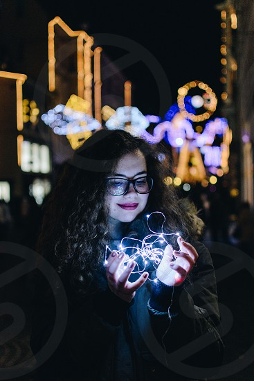 Woman in a dark city street holding fairy lights behind her there is a street full of christmas lights. photo