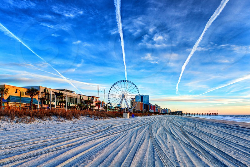 Photo of the beach featuring a boardwalk a Ferris Wheel and leading line patterns in the sand and in the blue sky above. photo