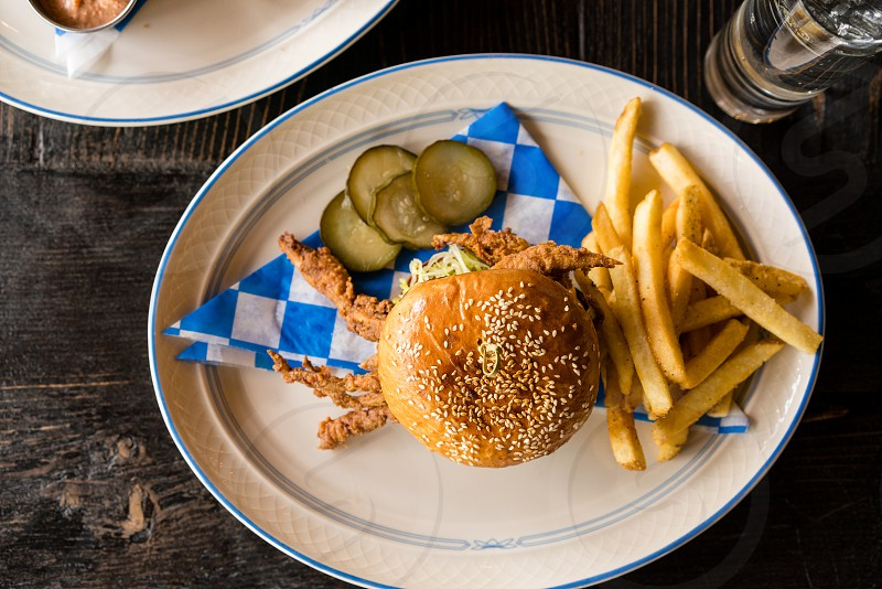 hamburger and fries on white ceramic oval plate with sliced pickles on the side photo