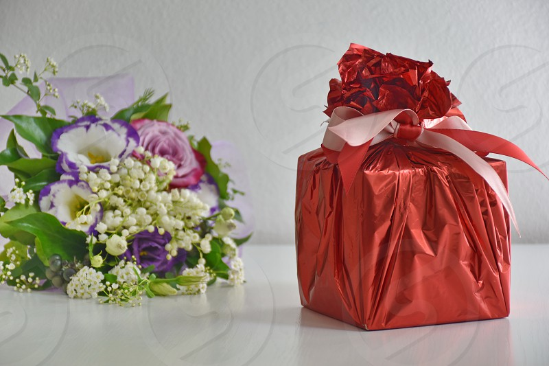Flowers and gift on white background photo