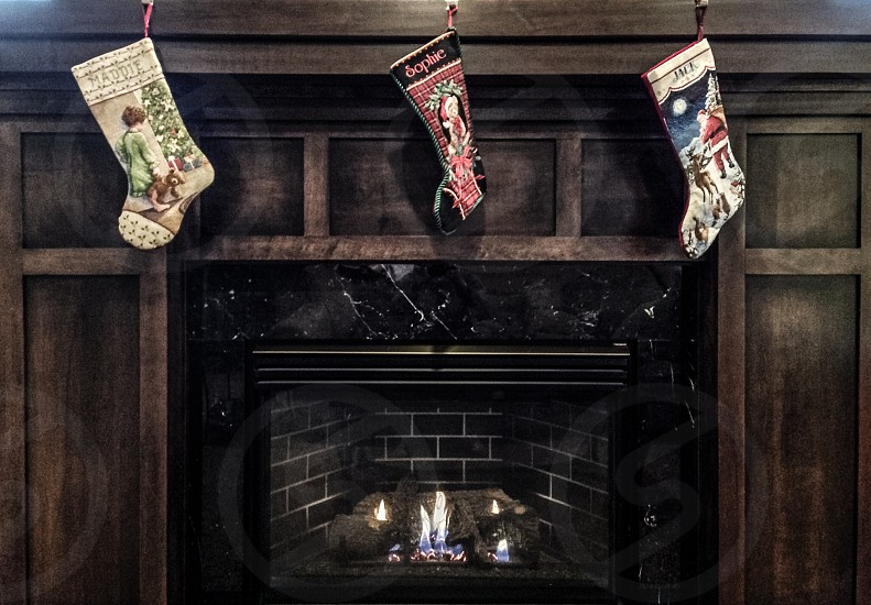 3 socks hang on fireplace photo