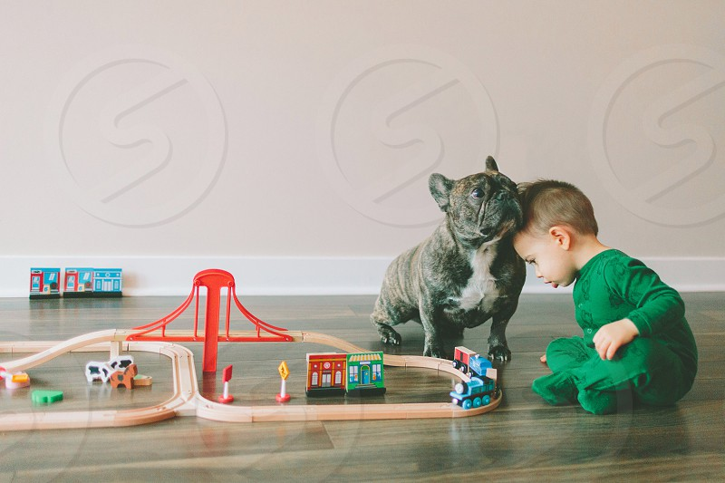 A little boy and his french bulldog sharing a moment while playing with a toy train set.  photo