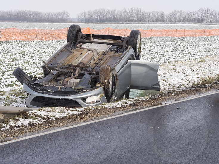 Overturned Car Beside the Wet Road on a Winter Day photo