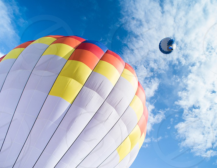 Multicolored Balloon in the blue cloudy sky photo
