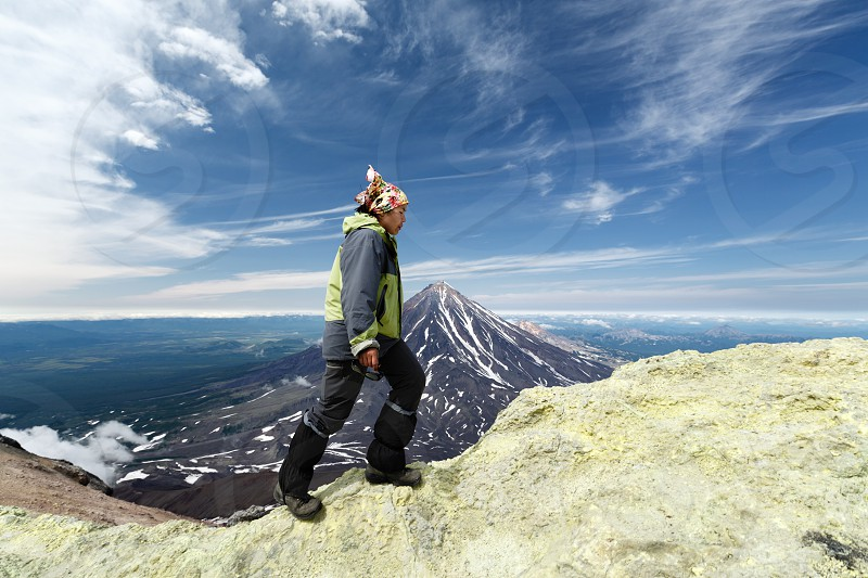 AVACHA VOLCANO KAMCHATKA PENINSULA RUSSIAN FAR EAST - AUG 7 2014: Young women tourists climb to sulfur fumarole field in crater of active Avachinsky Volcano on background of cone of Koryak Volcano. photo