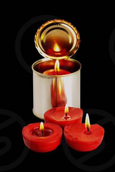 red candle on a tin can over black background photo
