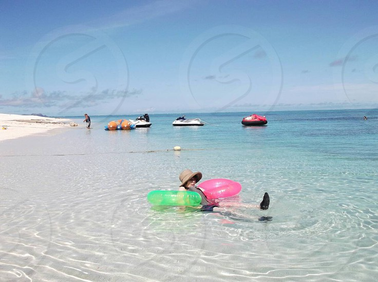 photo of person wearing brown sun hat with green and pink floaters at seashore photo