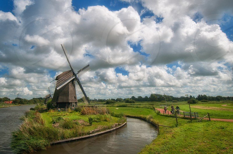 windmill in grass surrounded by water and field clouds in the sky photo