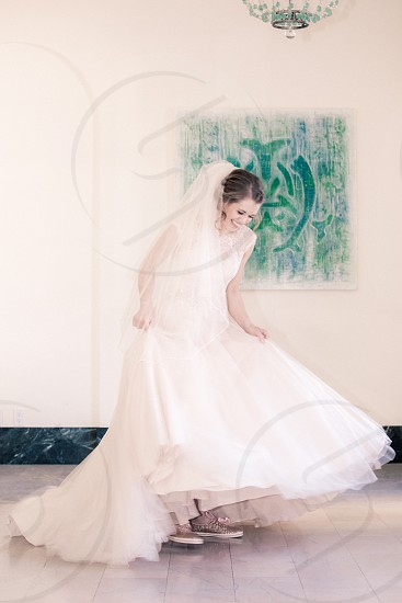woman in white veil white illusion shoulder floor length wedding dress grey low top sneakers beside the painting of tribal green under blue crystal chandelier photo