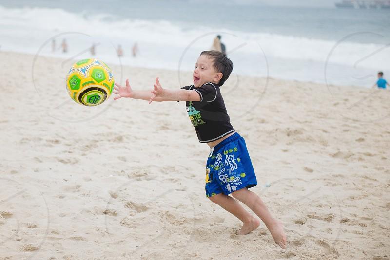 playing soccer ball boy beach photo