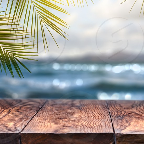 Beach background with palm coconut leaf and old wood table top on blurred beach background and view for promote product concept. . Concept Summer Relax and Party. photo
