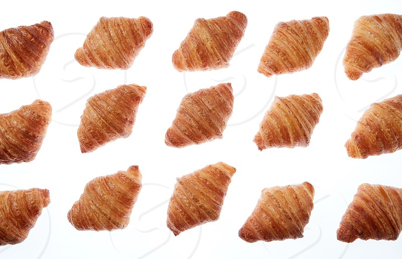 Freshly baked homemade delicious croissants pattern on a white background. Continental breakfast concept. photo