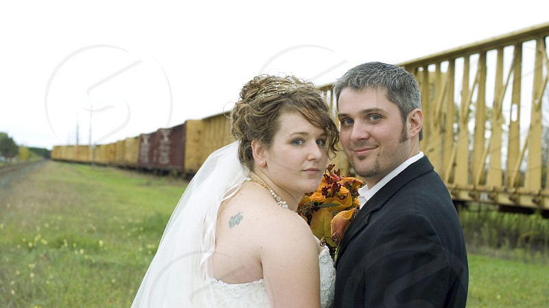 newly wed couple near yellow train rails during daytime \ photo