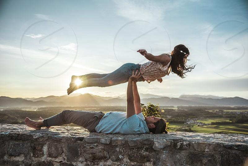 Man lifting his girlfriend while lying down. photo