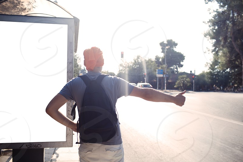 Man standing alongside a blank billboard on a bus stop on a street thumbing a lift backlit by a bright summer sun photo