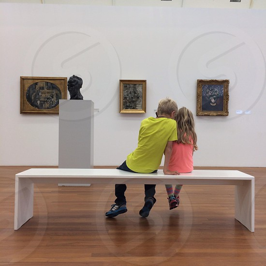 boy in yellow t shirt sitting beside a girl in pink shirt inside the museum photo