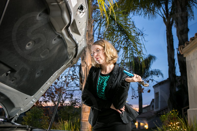 A woman works on her cars engine with channel locks while wearing a business casual outfit during twilight. photo