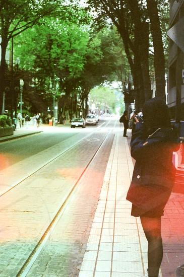 woman in black hoodie standing beside road taking photos photo