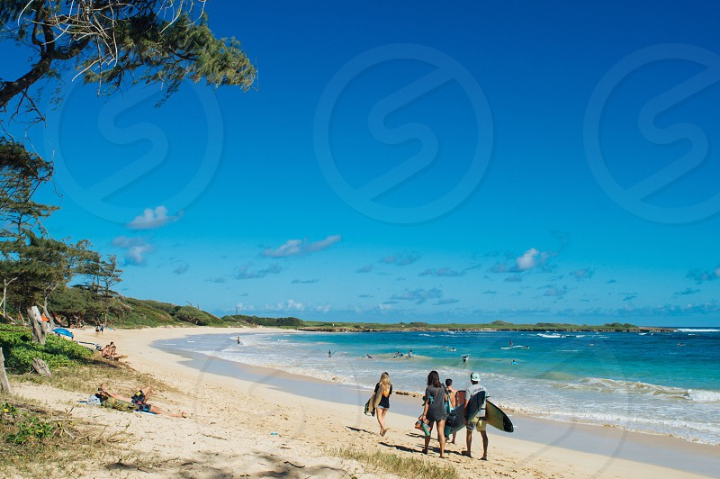 2 men and 2 women walking at the beach with surf boards photo
