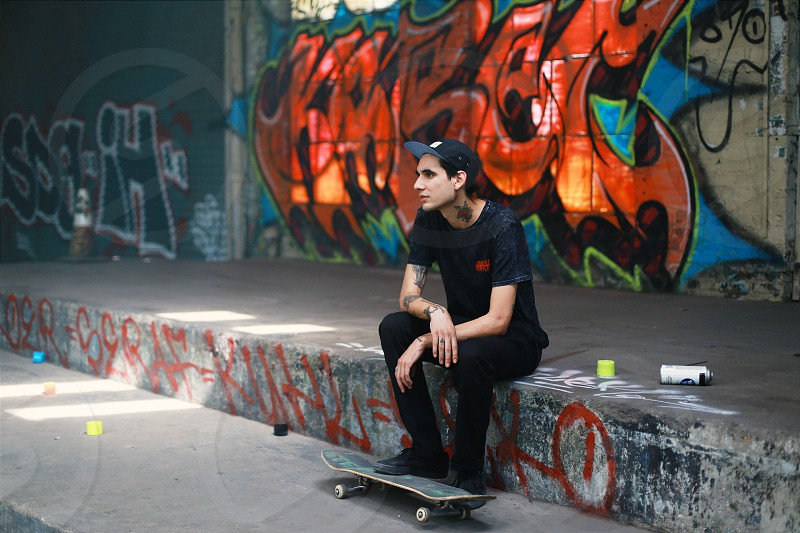 man with tattoos wearing a black baseball cap and black tee with black jeans sitting on a graffiti painted step with a skateboard under his foot and graffiti painted wall behind him photo
