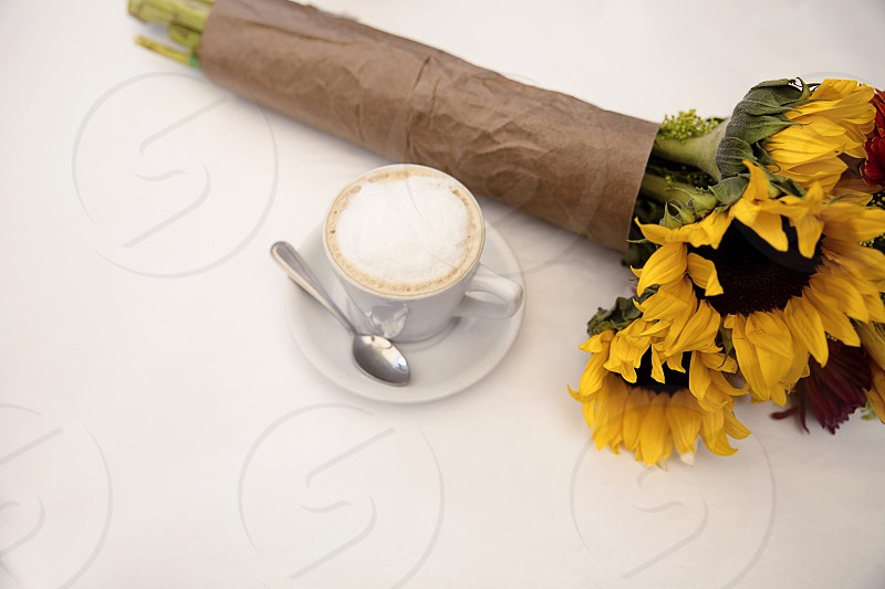 high angle photo of yellow sunflower bouquet beside white ceramic filled with coffee photo