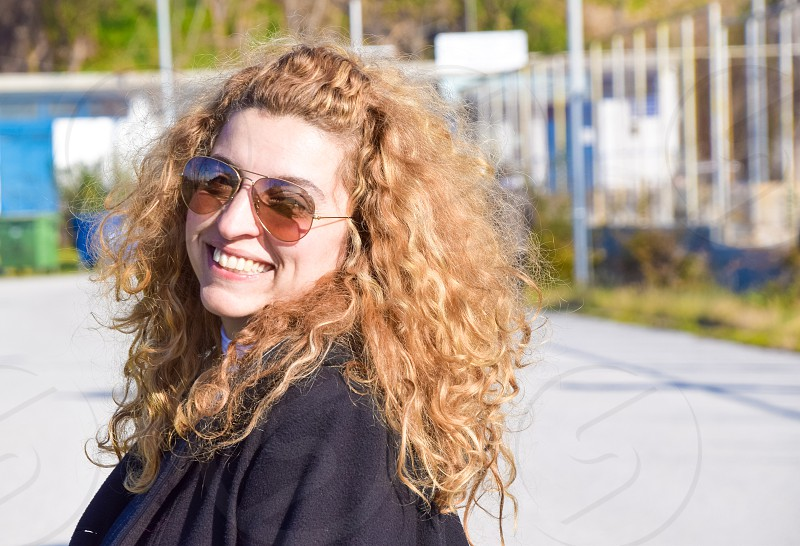 Young Beautiful Blond Woman With Curly Long Hair And Sunglasses photo