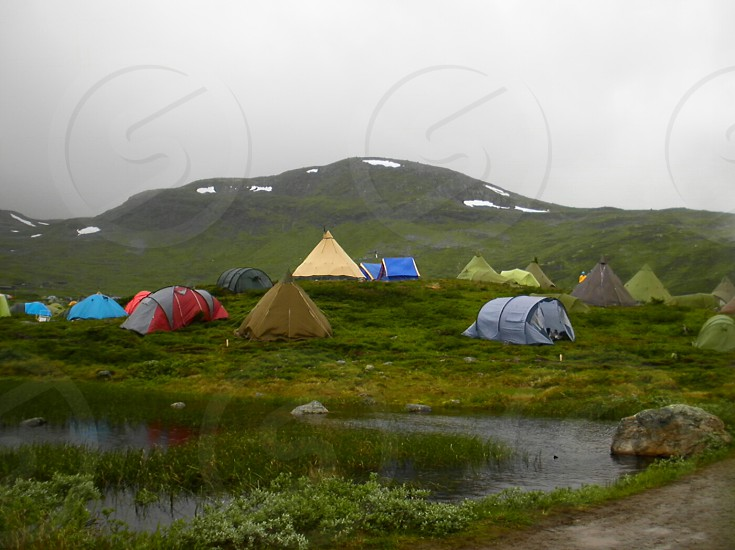 Camping tents mountains snow water river pond lake rock cloudy fog pasture grass green. photo