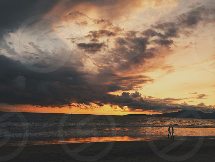 2 person walking on shore sunset view photo
